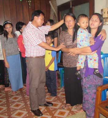 Kenneth and Eunice Praying for Church Member